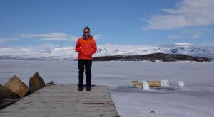 Dr. Silvie Harder on the dock near Arctic research station, with sauna dipping hole behind